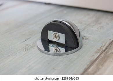 A door stop with a rubber damper and a built-in magnet is attached to the wooden floor.