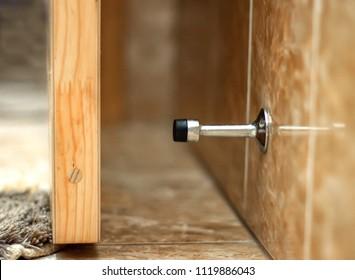 The door stopper. Stainless door stop. Close up, selective focus.