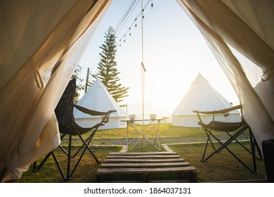 The door tent view lookout camping on the mountain in the morning. Glamping camping teepee tent with two empty chairs and table picnic front the door of tent.