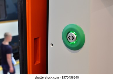 Door of train carriage with the electric green button press to open sliding mechanical door at a train station platform. Train door push button