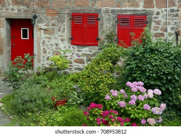 Door and two windows with red wooden shutters in an old stone facade with flower garden in the foreground