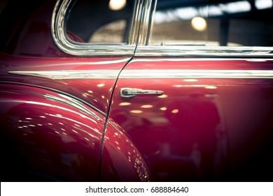 Door and window details of red retro car.