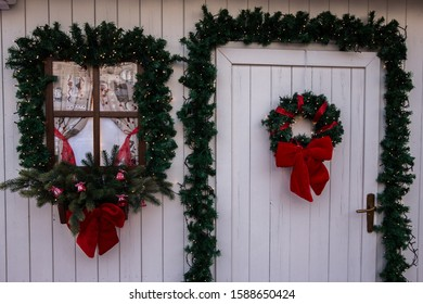 Door and window of a fake white house beautifully decorated for christmas
