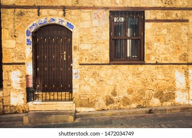 Door and window of an old house. The walls of the house are made of stone, and the windows and doors are made of wood. The house stands next to the road.