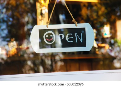 Door window sign open with smile hadwritting with chalk