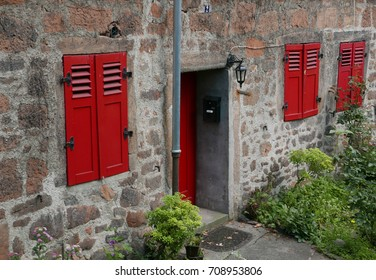 Door and windows with red wooden shutters in an old stone facade with flower garden in the foreground