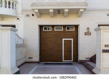 A door within a door. Entrance to a home through a wooden garage door in Birkikara, Malta. The comtrast between the white limestone walls and the brown wooden doors combines modern with traditional