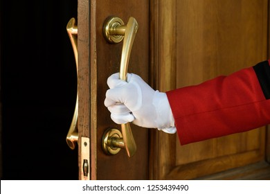 the doorman opens the hotel door hands in white gloves. Welcome