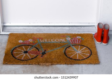 doormat welcome with red rain boots