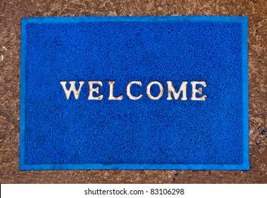The Doormat of welcome text on floor background