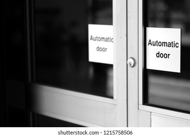 """Doors of glass and metal with a lock and signs with the words """"automatic doors""""."""