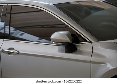 Doors mirror of new bronze car closed for safety at car park, Side mirror of gray car , black tinted glass