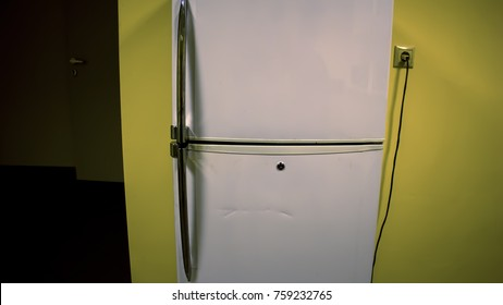 The doors of the white refrigerator near the yellow wall