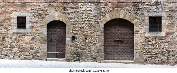 Puertas y ventanas en antiguas paredes de piedra medieval a lo largo de una calle en un pueblo toscano.