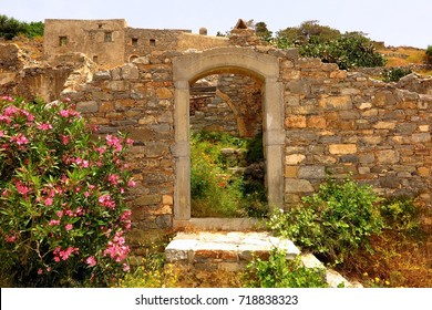 doorway to ruins with wildflowers on Spinalonga Island, Crete, Greece. Symbol of both decay and rebirth.