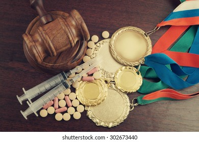 Doping in sport. Gavel, gold medals and tablets with syringes on table