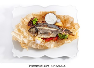 Dorado Baked with Tomato Salsa, Greens and Olives Isolated on White Background. Restaurant Exquisite Serving Dish of Whole Grilled Sea Bream Fish on Rustic Paper Close Up