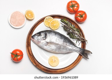 Dorado fish or gilt-head bream served on white plate on white background, flat lay, top view