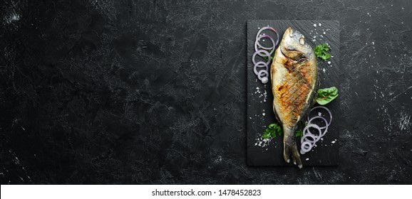 Dorado fish grilled on stone plate. Top view. Free copy space.