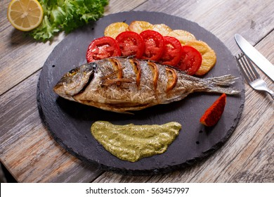 dorado fish on a granite board with potatoes and tomatoes