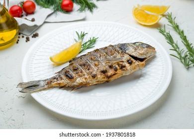 Dorado on grill on a white plate on white concrete table