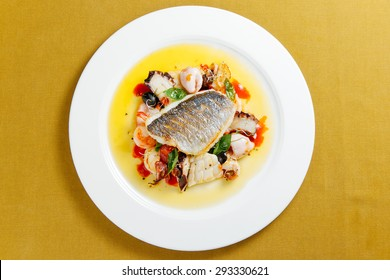 Dorado with seafood and cherry tomatoes on a white plate. Top view