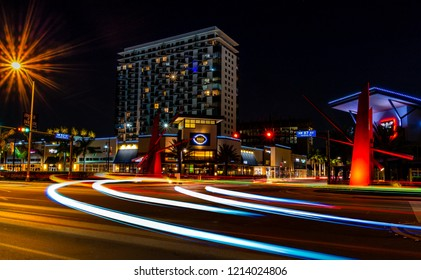 Doral, FL/USA-10/20/2018: Intersection of NW 87th Ave. and NW 53rd St. in Downtown Doral, FL showing local restaurants, condo tower in background and traffic light trails in foreground.