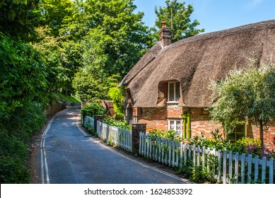 Dorchester, Dorset, England July 4 2011. Dorset cottage with a thatched roof in summer. Next to a road with a white fence