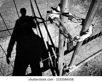 DORCHESTER, DORSET, UK - October 21 2018: Locked out. Perimeter fence with heavy padlock and chain. Keep out. No entry. Black and white photograph.