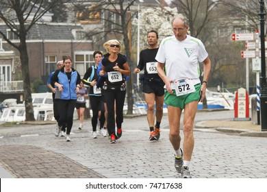 DORDRECHT, THE NETHERLANDS - APRIL 3: runners in 'Dwars door Dort' 10km race for all ages, in Dordrecht, The Netherlands on April 3, 2011