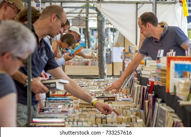 DORDRECHT, NETHERLANDS - JULY 7 2013: Choosing and looking for second hand books at the annual book market held in the centre of Dordrecht. The market attracts 75000 visitors annually.