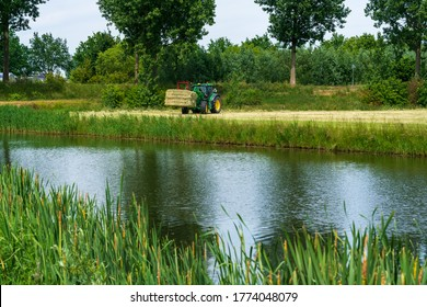 Dordrecht, Netherlands - June 1 2020: Green tractor loading bales of hay onto a trailer in rural countryside.The Biesbosch National Park is one of the largest national parks of the Netherlands