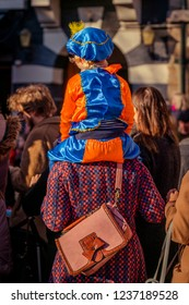 Dordrecht, Netherlands - November 17, 2018: Young child sitting on the shoulders of a parent while waiting for Saint Nicolaas to pass dressed in an orange and blue costume of Pete.