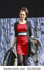 DORDRECHT, NETHERLANDS - SEPTEMBER 27 2015: Free entertainment fashion show in the main square organized by the municipality. Model in red outfit on the catwalk showcasing the new winter collection.