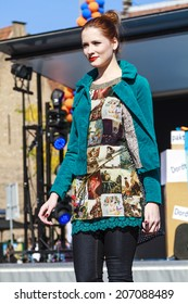 DORDRECHT, NETHERLANDS - SEPTEMBER 29 2013: Free entertainment and fashion show in the main square organized by the municipality. Model in green stands on catwalk showcasing the new autumn collection.