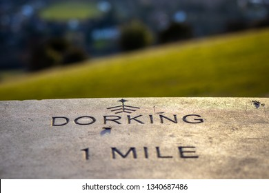 Dorking 1 mile sign with direction arrow. It's located on Hill Box England.