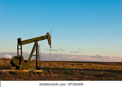 Dormant oil or natural gas pump alone on vast prairie with storm clouds in the distance