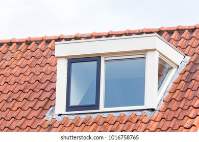 Dormer window on  roof of house with orange roof tiles