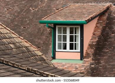 A dormer window on a tiles roof