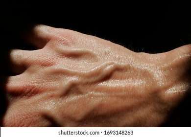 dorsal of a sweaty hand with many veins on a black background