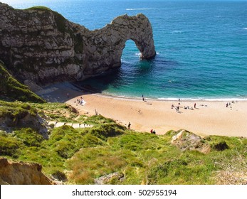 Dorset England Durdle Door limestone arch people walking on beach. Landmark attraction on Dorset's Jurassic Coast, UNESCO World Heritage Site