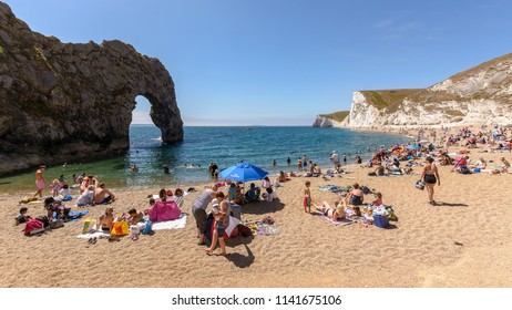 Dorset, England - July 23, 2018: Tourists Relaxing On Durdle Door Beach A, Dorset; Summer Time English Heat Wave 2018