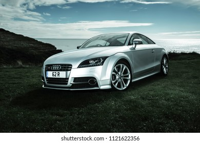 Dorset, England - May 10 2013: Audi TTS Coupe Mk II 2+2 sitting on Cliff top with sea and cloud in background. In August 2004, Audi announced that the next generation TT would be made of aluminium.