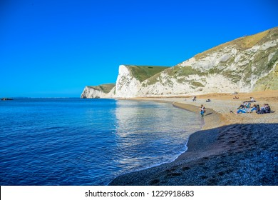 DORSET, ENGLAND - OCTOBER 19: Tourists enjoying their time at a beautiful view of Durdle Door, a natural limestone arch on the Jurassic Coast near Lulworth in Dorset, England, United Kingdom