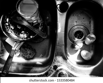 DORSET, UK - May 22 2018: Washing up left in a sink. Dirty frying pan, broken eggs, scourer. Black and white photograph.