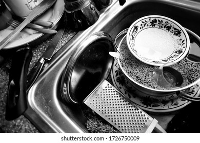 Dorset, UNITED KINGDOM - April 23 2020: Black and white close-up of kitchen washing-up and stainless steel sink, selective focus on details. Self-isolation, mental health.
