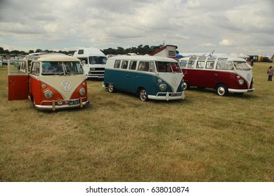 Dorset-July 13 2014: Three Colorful Camper Vans from 1960s on Display on Grass Field at VW Festival, Free Entry to Public, in Dorset