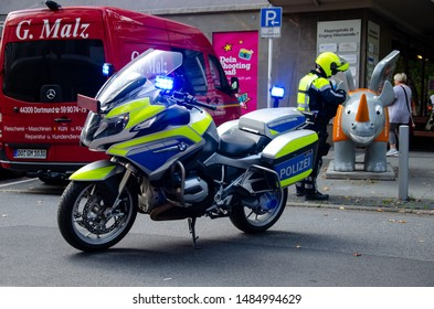 Dortmund, Germany - August 2, 2019: Policeman near motorcycle patrolling the streets.