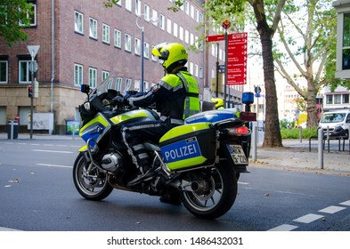 Dortmund, Germany - August 2, 2019: Policeman on motorcycle patrolling the streets. Motorcycle policemans on the street.