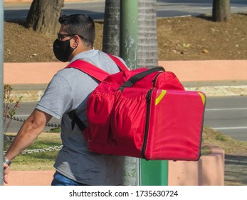 São José dos Campos - May 19, 2020: cyclist with fast-food delivery bag, wearing black mask, during the Covid-19 pandemic. Ifood